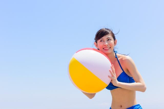 ビーチボールと水着の女性